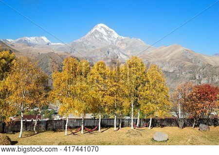 View Of Mount Kazbek In The Greater Caucasus Mountains Of Georgia With Yellow Autumn Trees And Hammo