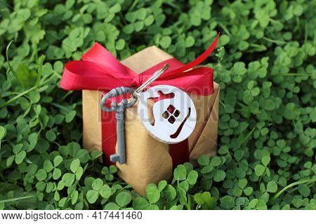 Gift Idea With Key Symbol And House On The Background Of A Green Lawn With Clover. Real Estate In Ec