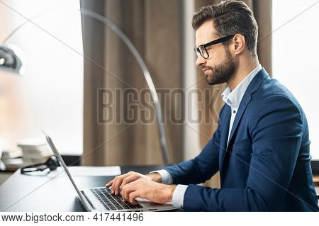 Engrossed Employee Working On Laptop At Home Office. Young Slavic Business Man Or Remote Teacher Usi