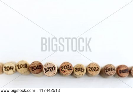 Wine Cork With The Number 2020 Stands Out Against The Background Of Blurry Corks With Other Years To