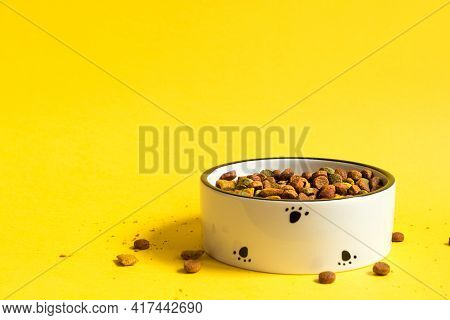 Pet Food Bowl With Dry Granulated Food On A Yellow Background. Food For A Cat Or Dog Is Poured Into