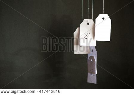 White Tags With The Percent Sign Hang On Strings On A Black Background With Shadows. Commerce, Disco