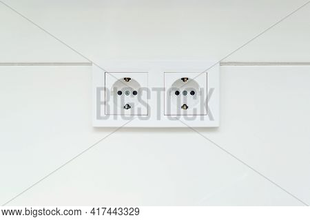 White Double Socket On Wall. Electrical Plug Into A Wall Socket. European Electrical Outlet On White