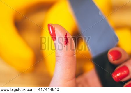 Female Hand With Red Manicure Holds Knife With Wounded Hand On Background Of Cutting Board With Pump