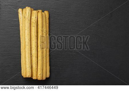 Homemade Italian Grissini Breadsticks On A Black Background. Traditional Italian Snack With Herbs.