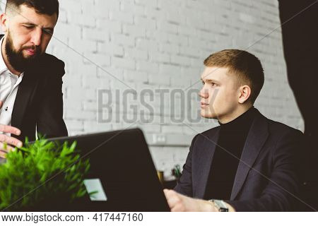 A Team Of Young Businessmen In Suits Working And Communicating Together In An Office. Corporate Busi