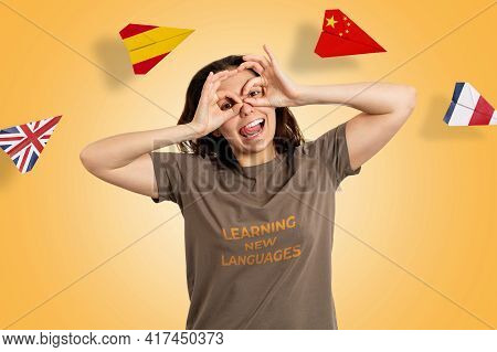 English Language Day. Portrait Of A Woman Making A Funny Grimace On Her Face. Yellow Background And