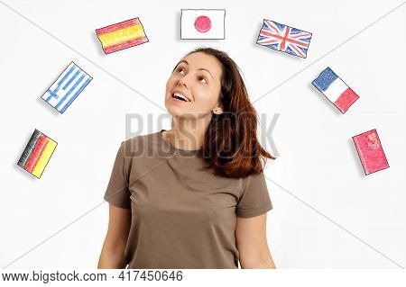 The Concept Of Learning Foreign Languages. Portrait Of Young Smiling Woman Looks At The Flags Of Dif