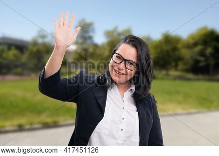 Cheerful Adult Businesswoman Wearing Glasses Or Spectacles And Smart Casual Office Suit Waving Hand