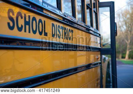 School District Written On The Side Of A School Bus. Door Is Open. No People, Nature Background.