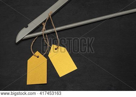 Wooden Hanger With Yellow Paper Labels. Black Background. Blank Label Mockup . Clothing Tag.
