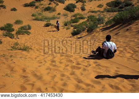 Utah / Usa - August 22, 2015: Boys Playing With A Surf In A Dunes Area In Coral Pink Sand Dunes Stat