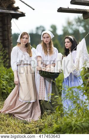 Countryside Lifestyle Concepts. Three Tranquil Caucasian Girls Together In Traditional Rural Dress W