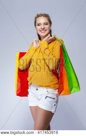 Shopping Ideas. Portrait Of Positive Caucasian Girl Posing With Plenty Of Colorful Shopping Bags Aga