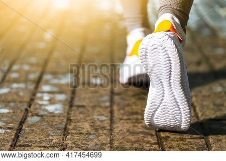 Jogging And Running Concept. Closeup Of Active Female Runner Feet During Running Exercise Outdoor. H