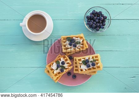 Waffles With Cream Cheese And Blueberries On A Pink Plate, Coffee Cup On Turquoise Wooden Table. Top