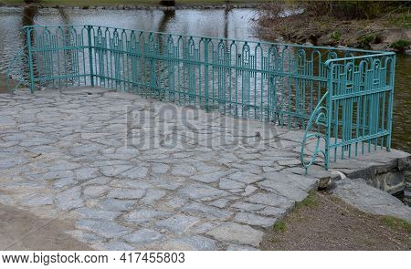 Details Of The Edge Of The Pond With Paved Banks Flat Stones. Curved Shape. The Path Is Lined With W