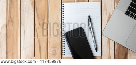 Top View Office Desk With Pen, Smartphone, Computer Laptop And Blank Notebook On Wood Table Backgrou
