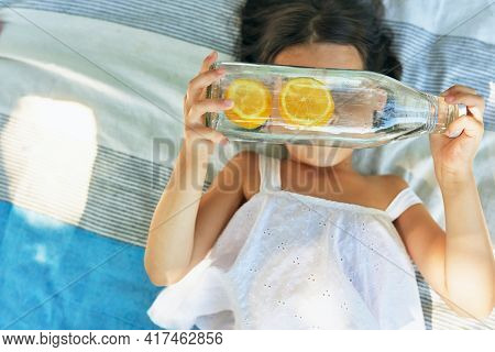 Top View Of A Little Girl Lying On The Picnic Blanket Looking Through Bottle Of Glass With Water Wit