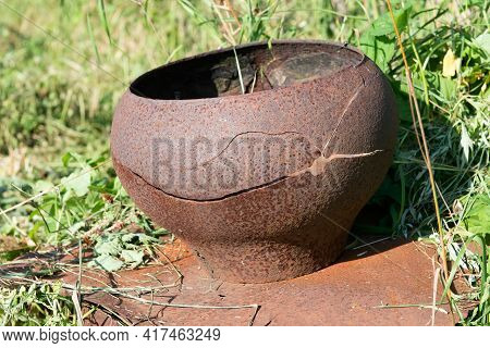 An Old Cast-iron Pot Stands Outside On The Grass. Old Rustic Cast Iron Utensils. Dirty Cast Iron Pot