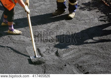 Road Street Repairing Works. Construction Workers During Asphalting Road. Manual Labor In Constructi