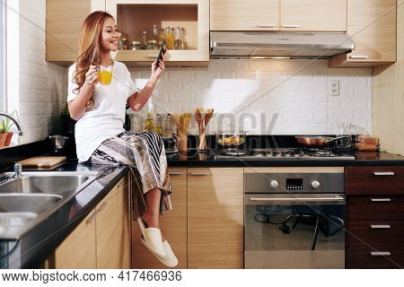 Happy Young Asian Woman In Loungewear Sitting On Kitchen Counter, Drinking Orange Juice And Reading