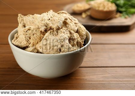 Dehydrated Soy Meat Chunks In Bowl On Wooden Table, Closeup