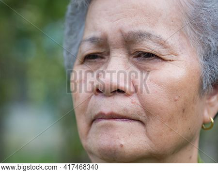 Close-up Of Face Elderly Woman With Short White Hair, Feeling Worry And Standing In Garden. Asian Se