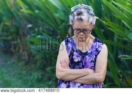 Portrait Of An Elderly Woman Hair Curlers, Arms Crossed And Looking Down While Standing In A Garden.