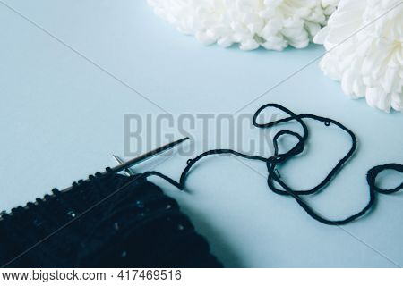 Unwound Thread. Knitting Black Yarn And A Ball Of Thread And Knitting Needles And White Flowers Peon