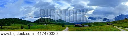 Panorama Of Alpine Pasture With Wood And Mountain Range Background