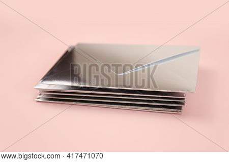 Stack Of Mirror Or Silver Paper Festive Envelope On Pink Isolated Background. Envelopes For Invitati