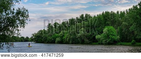 Beautiful Summer Landscape With A River And Green Trees On The Shore. Unrecognizable Persons Kayakin