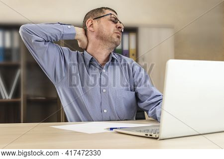 Tired Boss Businessman Clings To The Neck At The Desk, Experiences Neck Pain, Crabbing For The Tired