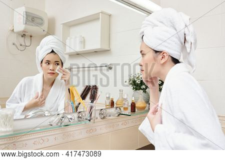 Pretty Young Asian Woman Applying Brightening And Hydrating Toner On Face With Cootton Pad