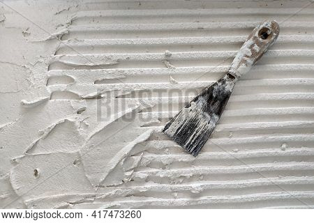 Installation Of  Ceramic Tiles. Tools For Laying Tiles- Trowel, Toothed Spatula. Glue For A Tile Wit