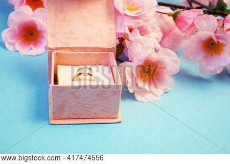 Wedding Ring In A Gift Box And Tree Blossom Flowers Branch, Wedding In Spring Time Concept, Closeup