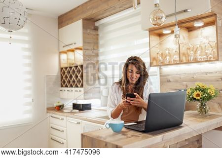Beautiful Young Woman Sitting At Kitchen Counter, Typing A Text Message Using A Smart Phone And Drin
