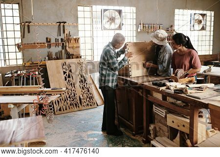 Experienced Senior Carpenter Examining Wooden Board With Cut Out Details Made With His Young Apprent