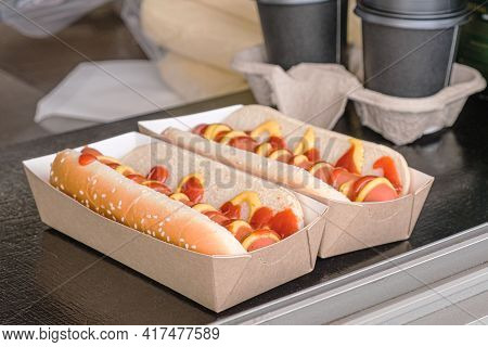 Two Hot Dogs In A Cardboard Box And Two Cardboard Cups Of Coffee On The Counter Of A Street Food Tak
