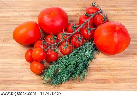 Cluster Of Fresh Ripe Red Cherry Tomatoes Among The Ordinary Tomatoes And Bundle Of Dill On The Bamb