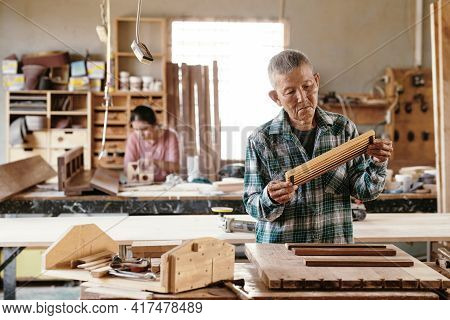 Serious Experienced Carpenter Standing At Workbench And Checking Finished Wooden Item