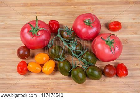 Multicolored Fresh Ripe Cherry Tomatoes On Branch And Separately, Ordinary Pink Tomatoes On A Wooden