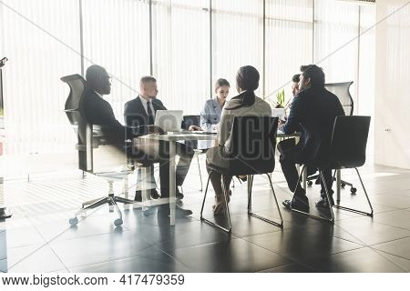 Silhouettes Of People Sitting At The Table. A Team Of Young Businessmen Working And Communicating To