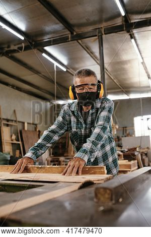 Experienced Elderly Carpenter In Earmuffs Cutting Long Wooden Board With Circular Saw