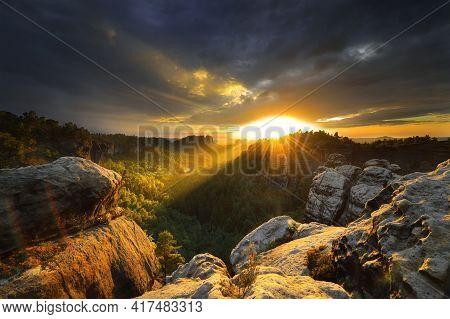 Saxon Switzerland Elbsandstone Dark Cloudy Sunset At National Park Rock Peak Above Forest