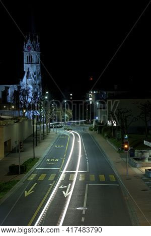 Downtown Area With A Main Street And An Illuminated Church In The Background At Night In Vaduz In Li