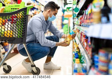 Middle-eastern Man Doing Grocery Shopping Choosing Cooking Oil In Supermarket