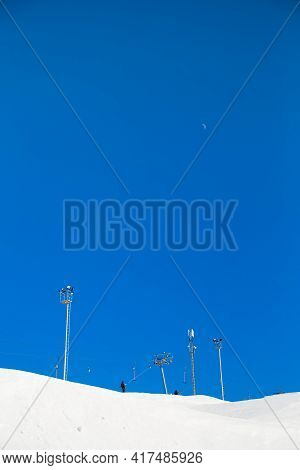 Ski Resort, Gentle Snow Slope With Lighting Towers And A Moon In The Sky. Mountain Slope For Skiing