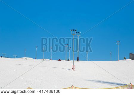 Ski Resort, Snow Slope, Trail With Towers And Floodlights. Mountain Slope For Skiing And Snowboardin